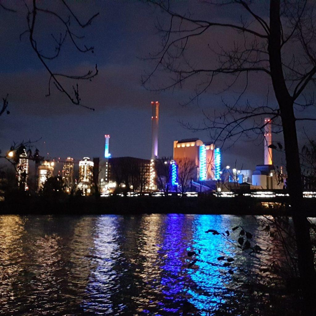 Das Bild zeigt die Skyline von Frankfurt bei Nacht. Die Lichter der Hochhäuser spiegeln sich im Main.